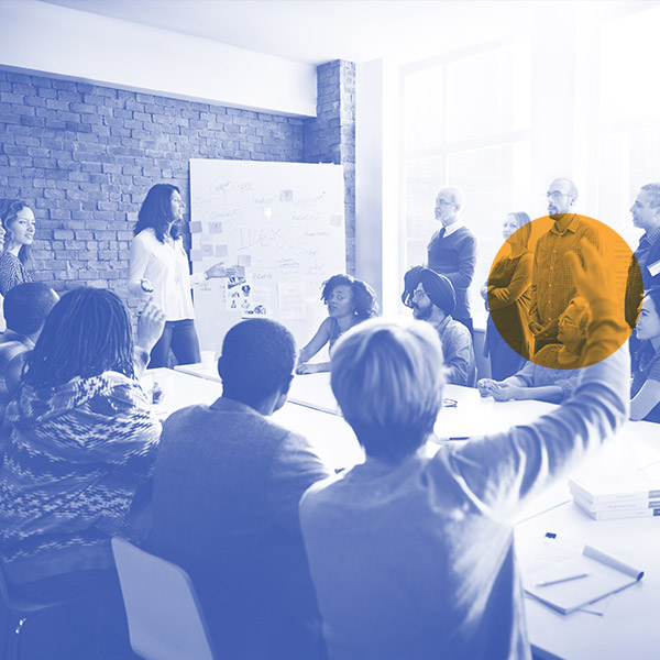 Diverse group in an open meeting room with presenter